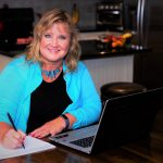 Lynne Edris at table with laptop and calendar